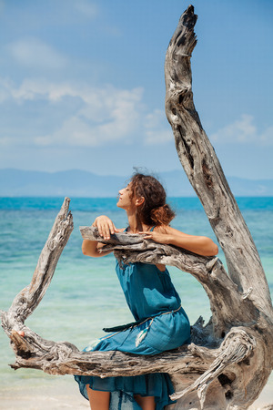 snag: attractive young beautiful girl sitting on snag on beach Stock Photo