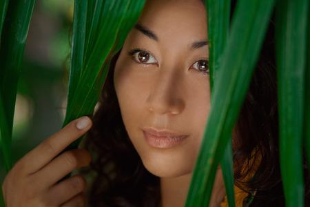 Portrét krásné asijské dívky v zelené listí