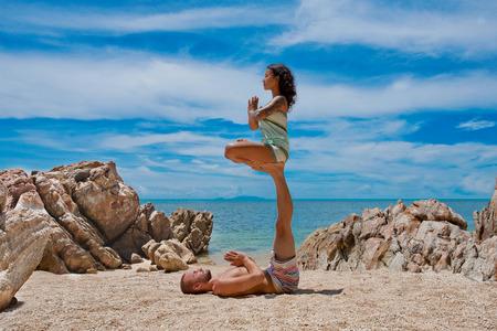 beautiful couple doing acro yoga on the beach