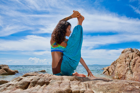 beautiful young woman doing yoga on the beach