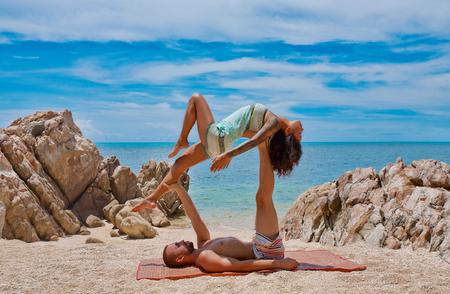 Krásný pár dělá akro jóga na pláži Reklamní fotografie