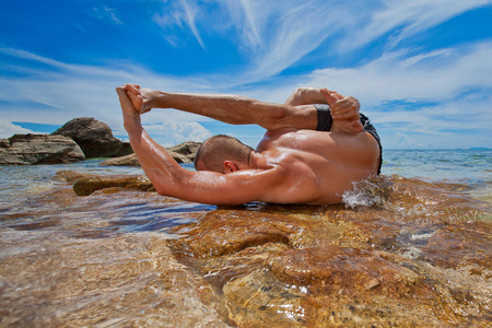 Člověk dělá jógu na pláži