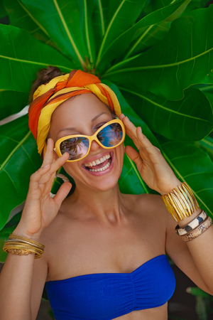 beautiful laughing girl with tropical leaves background