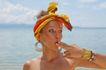 Stylish young woman with turban on the beach