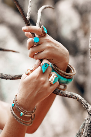 close up of woman hands with boho accessories