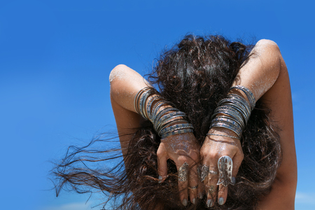 hands of young woman with boho accessories on the beach close up