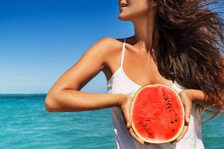 young woman having fun with watermelon on the beach