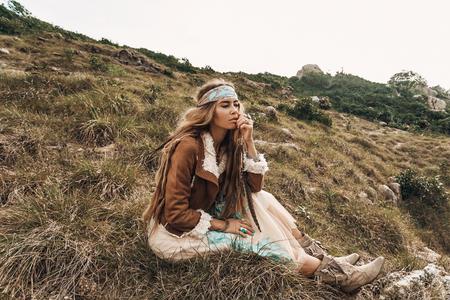 beautiful young boho girl in jacket sitting on a field Reklamní fotografie