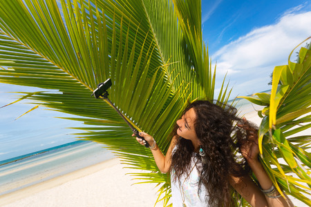 beautiful young woman taking selfie with selfie stick on the beach Reklamní fotografie