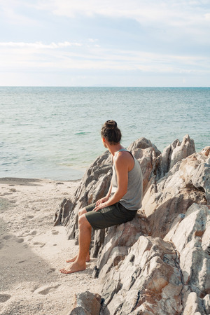 young man sitting on the beach and look on the horizon line
