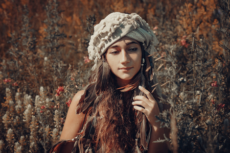 beautiful young woman with turban on a field at sunset Reklamní fotografie