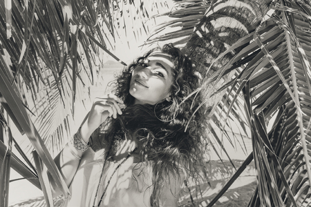 Beautiful woman in the shade of palm tree on beach
