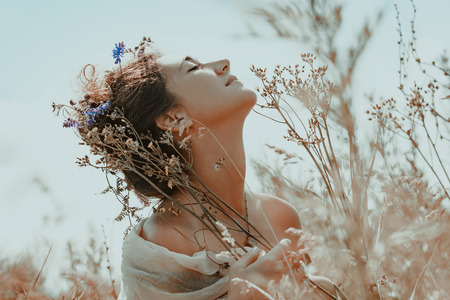 beautiful young woman with eyes closed on a field at sunset