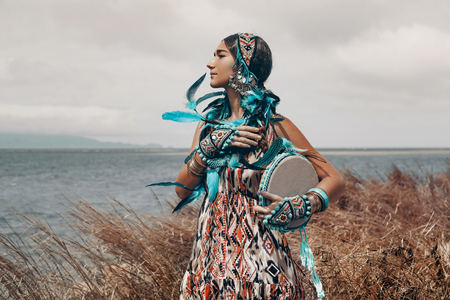 An attractive young woman in ethnical costume on a field at the sea 스톡 콘텐츠