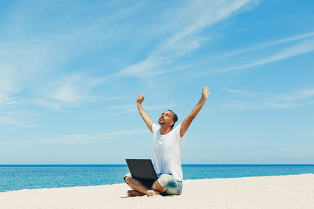 young man with laptop on the beach
