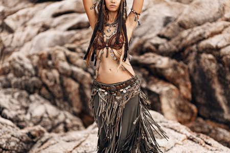 beautiful tribal woman dancer at stone background outdoors