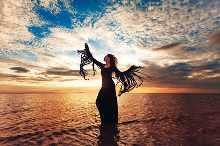 Elegante mujer bailando en el agua. Puesta de sol y silueta