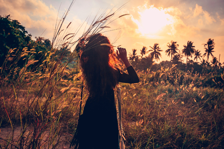 sunset portrait of beautiful young woman on a field Banque d'images