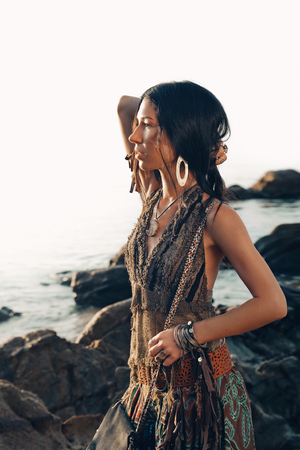 boho style young woman outdoors portrait at sunset on the beach Stock Photo