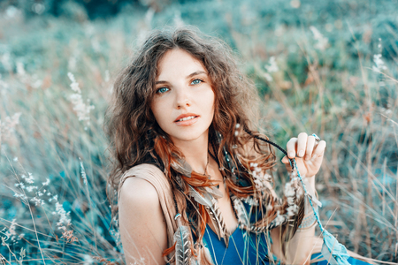beautiful young boho styled woman on a field at sunset
