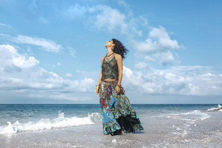beautiful young boho woman walking by the shore line through the waves