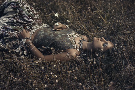 beautiful young eastern girl in ethnical jewelry lying on a grass on a field