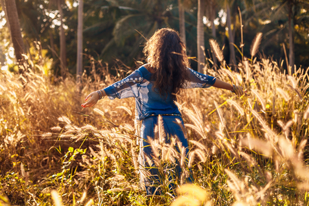 cheerful beautiful young woman having fun on a field at sunset