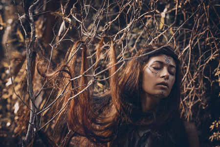 Beautiful young woman model with very long hair on branches. witch craftconcept