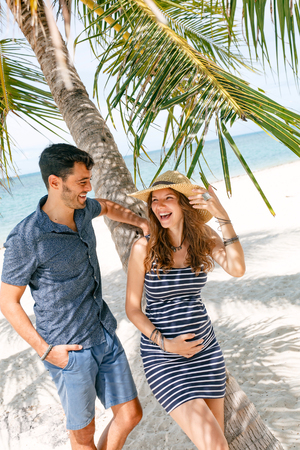 cheerful happy pregnant woman and husband having fun on the beach