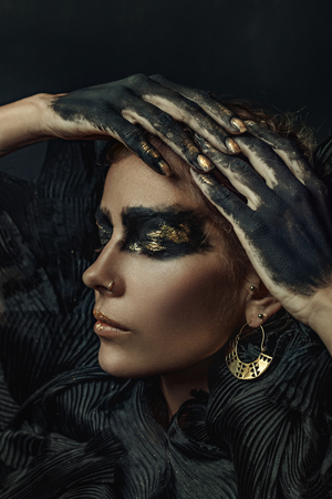 conceptual portrait of beautiful fashion look woman dark make up with gold