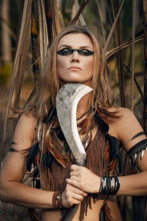 amazon warrioir fashion model makeup outdoor portrait with machete Reklamní fotografie