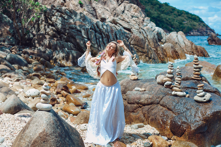 beautiful young boho style woman in white dress on stone beach