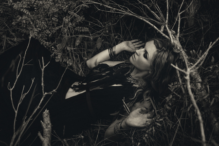 Beautiful young woman model portrait in forest. witchcraft concept