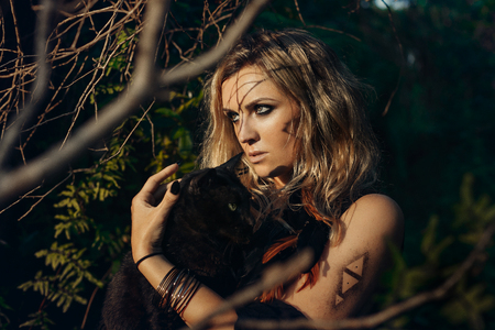 Beautiful young woman model portrait with black cat in forest. witchcraft concept Reklamní fotografie