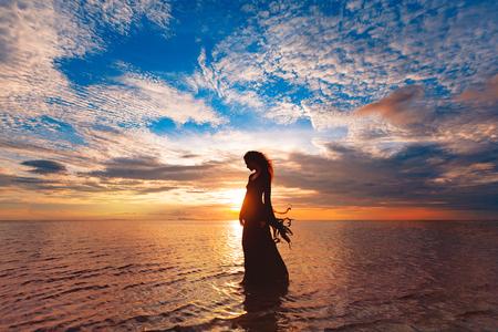 Mujer elegante bailando sobre el agua. Puesta de sol y silueta Foto de archivo