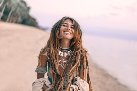 young beautiful boho woman portarait with traditional ornament on the beach at sunset Foto de archivo