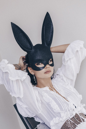 young woman in bunny mask in chair