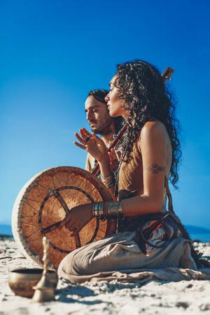 Hermosa joven pareja tocando música étnica con tambores de chamán al aire libre