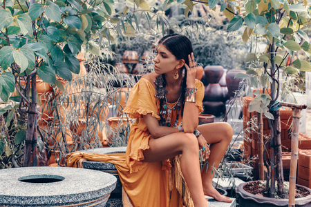 beautiful young fashionable woman with make up and stylish boho accessories posing on natural tropical background