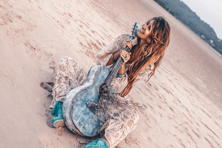 beautiful young cheerful fashion model in white dress with guitar having fun outdoors at sunset