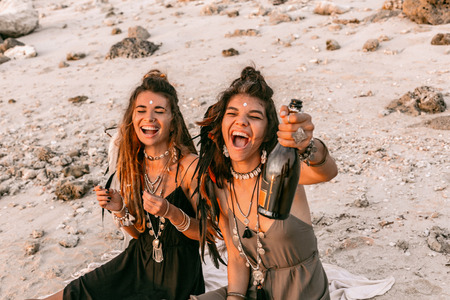 two beautiful young cheerful woman having fun at sunset with champagne