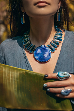 Close up of young woman wearing gem stone jewellery outdoors