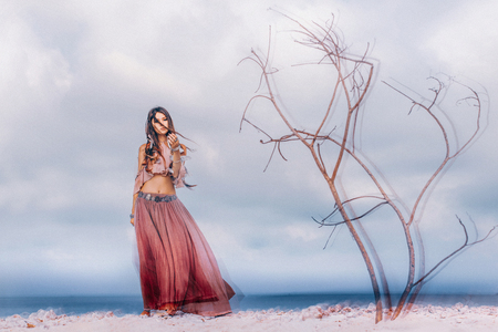 Beautiful young boho style woman outdoors with dry branches. Spiritual concept Stock Photo