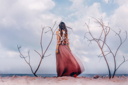 Beautiful young boho style woman outdoors with dry branches. Spiritual concept. Double exposure