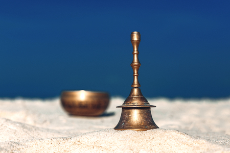 Bell singing bowl on the sand. Musical instruments  on the beach