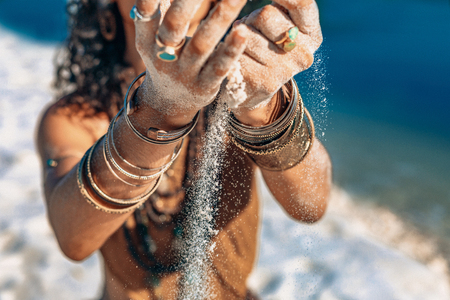 beautiful young woman holding sand in her hands on the beach