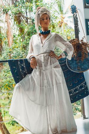 beautiful young boho woman wearing turban and white dress outdoors