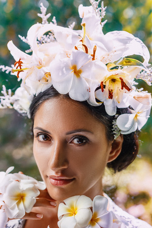 close up portrait of beautiful young woman wearing wreath made of frangipani flowers