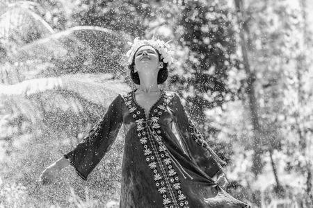 beautiful young stylish woman wearing wreath having fun under summer rain 스톡 콘텐츠