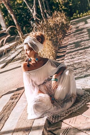 beautiful young fashionable woman in turban outdoors at sunset Stock Photo